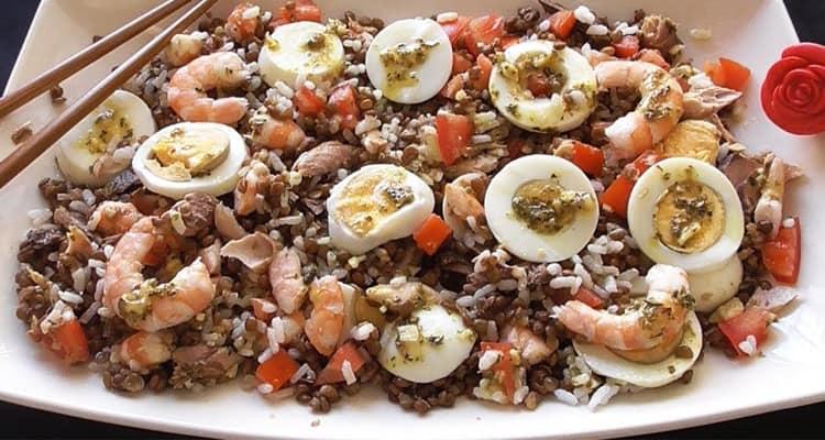 Plato con ensalada de lentejas, con langostinos, huevos cocido cortado en rodajas, tomate y caballa