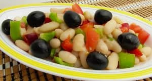 Un plato con una ensalada de alubias, pimiento verde, pimiento rojo y aceitunas negras