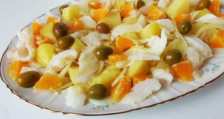 Un plato con una ensalada, contiene naranja, aceitunas verdes, bacalao y patatas
