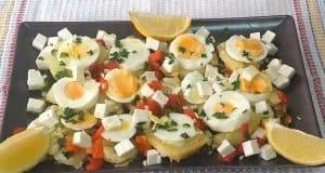 Ensalada en un plato cuadrado con patatas, queso fresco, huevo, pimiento morrón y unos gajos de limón en ambas esquinas del plato.